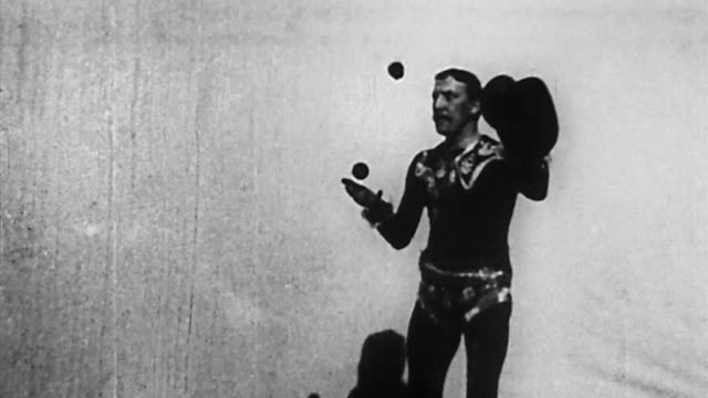 1895 medium shot german vaudeville performer juggling 3 balls and top hat - jonglieren stock-videos und b-roll-filmmaterial
