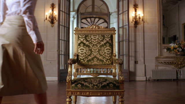 Medium shot gilded chair with velvet tapestry in foyer of mansion / young woman sitting down in chair
