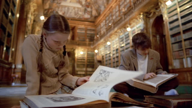 Medium shot girl and boy reading books in Philosophical Hall library at Strahov Monastery / Prague