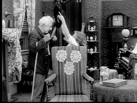 1913 b/w medium shot girl bringing grandfather his hat, adjusting his tie and kissing him before he leaves living room / usa  - 1913 stock videos & royalty-free footage