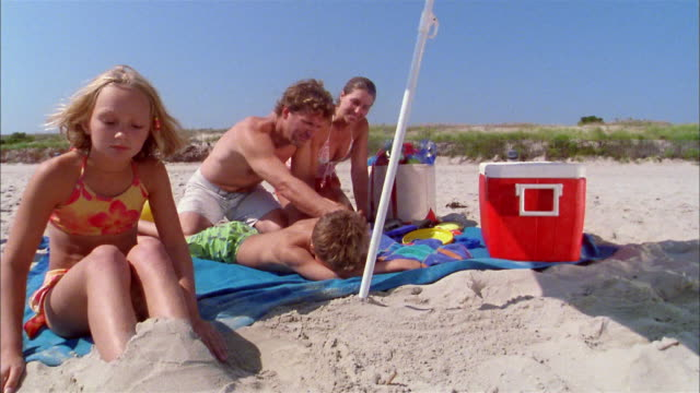 medium shot girl burying her legs in sand w/family sitting on beach towel in background - cool box stock videos and b-roll footage