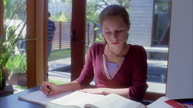 medium shot girl doing homework / boy entering house in background - secondary school child stock videos & royalty-free footage