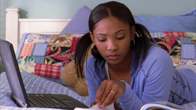 vidéos et rushes de medium shot girl doing homework w/laptop computer in bed - peluche