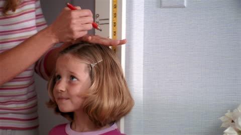medium shot girl getting height measured - instrument of measurement stock videos & royalty-free footage