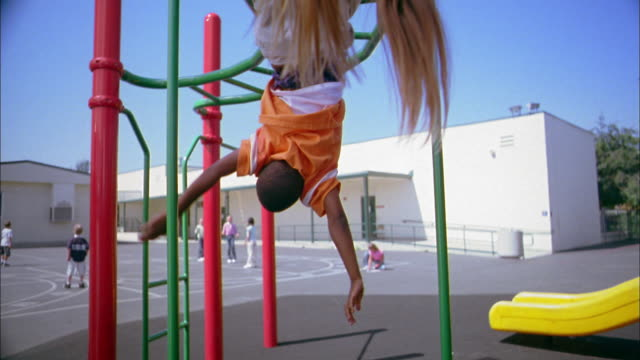 medium shot girl hanging upside down on playground monkey bars / boy hanging upside down in background - ジャングルジム点の映像素材/bロール