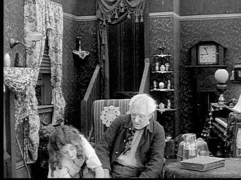 1913 b/w medium shot girl helping grandfather out on his boots in living room / usa  - 1913 stock videos & royalty-free footage