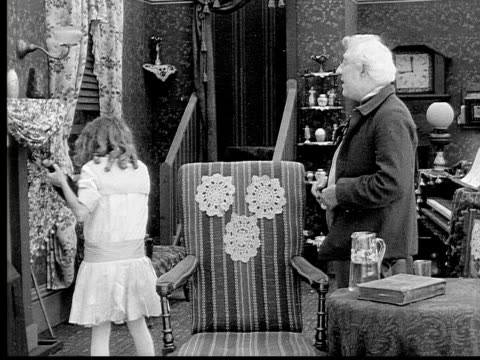 1913 b/w medium shot girl hiding liquor bottle for grandfather in grandfather clock in living room / usa  - 1913 stock videos & royalty-free footage