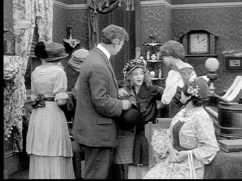 1913 b/w medium shot girl hugging father as group of women talk in living room / usa  - 1913 stock videos & royalty-free footage