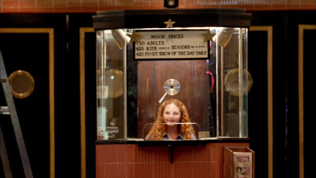 Medium shot girl in movie theater box office selling ticket to woman / Seattle, Washington