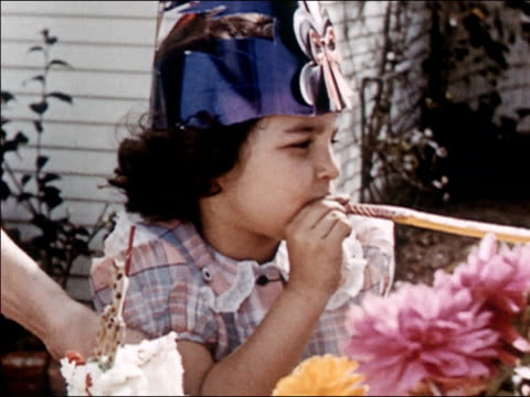 1954 medium shot girl in party hat blowing noisemaker / turning towards birthday cake / audio - party hat stock videos and b-roll footage