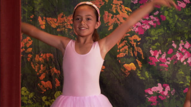 Medium shot girl in tutu posing, turning and curtsying / pan three other ballerinas standing on stage