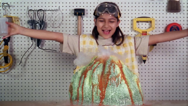 Medium shot girl making volcano model in shed / smiling at dry ice 'erupting' from volcano and posing for CAM