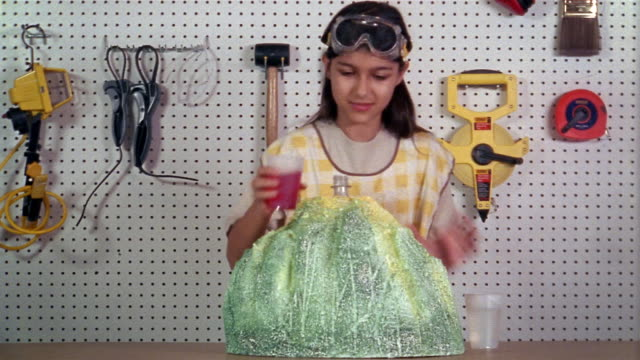 Medium shot girl making volcano model in tool shed