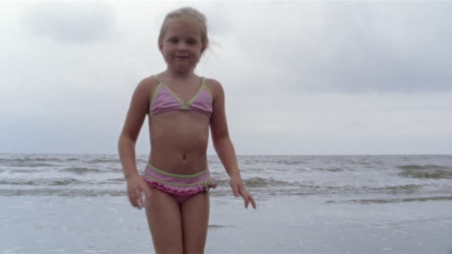 stockvideo's en b-roll-footage met medium shot girl on beach waving at camera/ wide shot girl running away/ charleston, south carolina - medium filmcompositietype