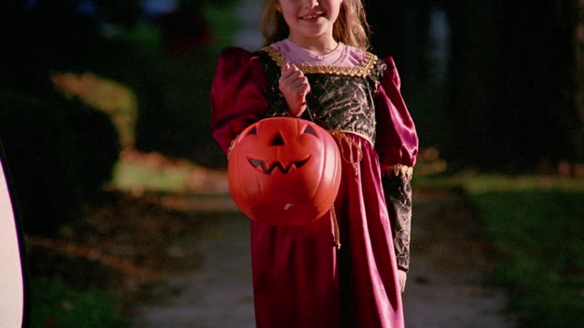 Medium shot girl posing in princess costume and holding pumpkin candy collector / Pennsylvania