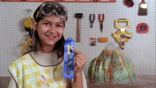 Medium shot girl posing with blue ribbon next to model of erupting volcano