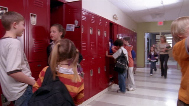 medium shot girl putting things in primary school locker/ pan wide shot girl walking by lockers and through doorway with boy/ goram, maine - korridor stock-videos und b-roll-filmmaterial