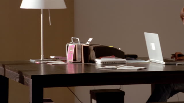 medium shot girl reading book on bench at end of table / pan across table to mother working on laptop - fax machine stock videos & royalty-free footage