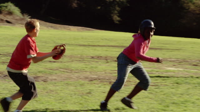 Medium shot girl running bases / getting caught between two basemen / baseman tagging her out