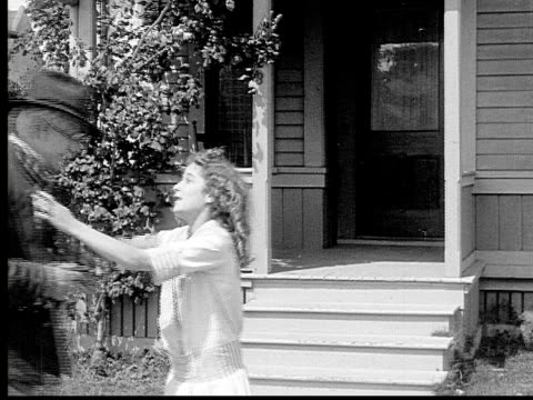 1913 b/w medium shot girl running down porch steps to meet grandfather and helping him inside house / usa  - 1913 stock-videos und b-roll-filmmaterial