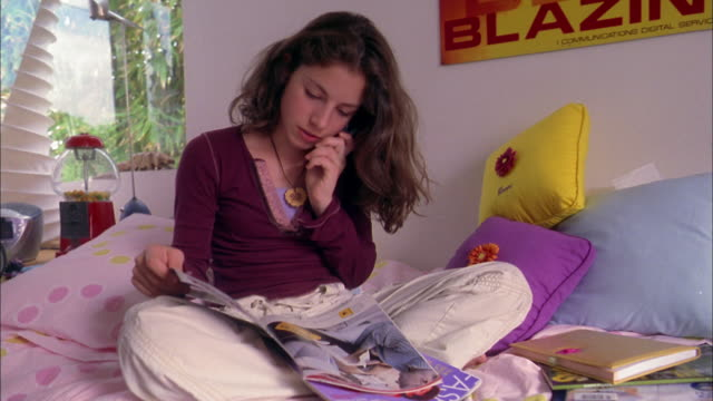 stockvideo's en b-roll-footage met medium shot girl sitting in bed and reading magazine / answering mobile phone - magazine