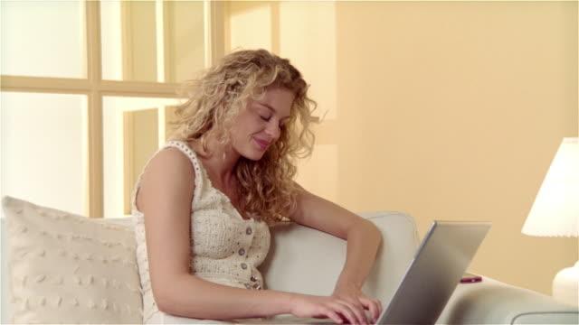 medium shot girl sitting on sofa, using laptop - nur weibliche teenager stock-videos und b-roll-filmmaterial