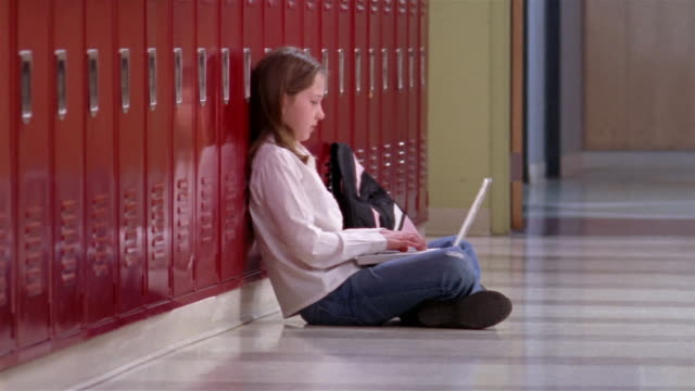 medium shot girl sitting, typing on laptop against school lockers/ goram, maine - child sitting cross legged stock videos & royalty-free footage