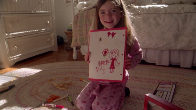 medium shot girl smiling and holding up homemade drawing to cam - human face drawing stock videos & royalty-free footage