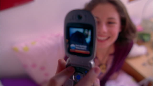 medium shot girl smiling and taking photograph of herself w/camera mobile phone - 2004 stock videos & royalty-free footage