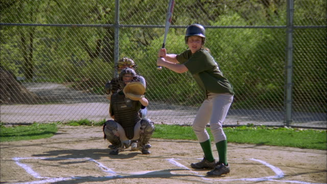 stockvideo's en b-roll-footage met medium shot girl swinging at pitch and missing for strike in game - baseball uniform