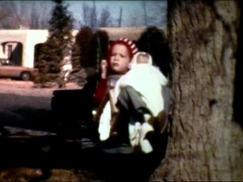 vidéos et rushes de 1975 medium shot girl swinging on swing while holding doll - seulement des petites filles