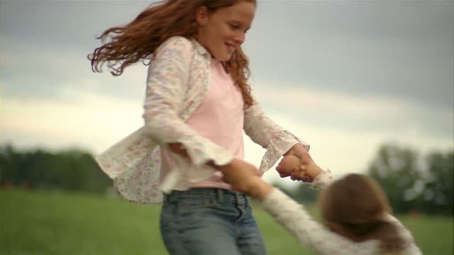 vídeos de stock e filmes b-roll de medium shot girl swinging younger girl around in field - irmãos
