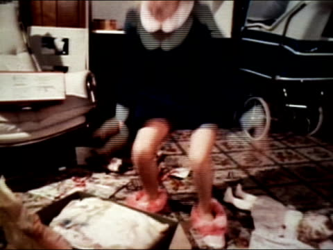 1977 medium shot girl trying on fuzzy slippers received as hanukkah gift/ girl dancing around - slipper stock videos and b-roll footage