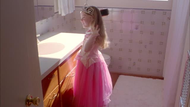 Medium shot girl wearing crown brushing her hair in bathroom mirror