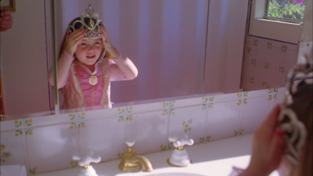 medium shot girl wearing princess dress and crown adjusting crown in bathroom mirror - crown headwear stock videos and b-roll footage