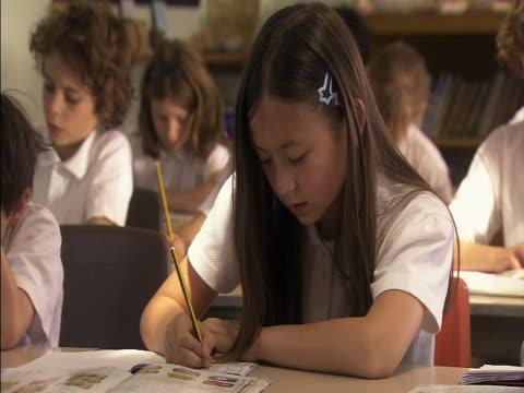 medium shot girl writing in notebook in classroom/ london, england - endast flickor bildbanksvideor och videomaterial från bakom kulisserna