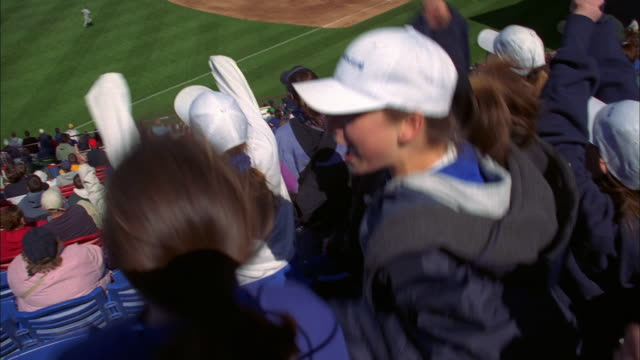 stockvideo's en b-roll-footage met medium shot girls in crowd jumping and cheering at baseball game - honkbal teamsport