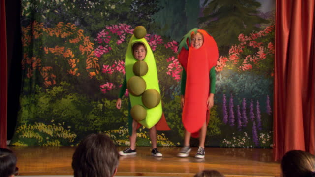 medium shot girls in pea pod and carrot costumes dancing on stage / woman taking photos - pacific islander background stock videos & royalty-free footage