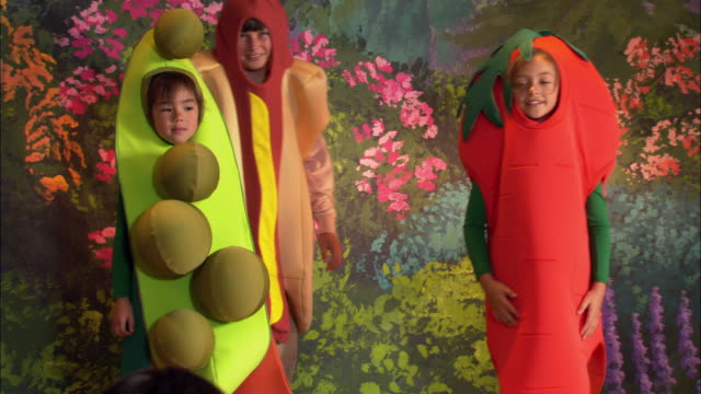 medium shot girls in pea pod and carrot costumes holding hands on stage / boy in hot dog costume joining them / zoom out taking a bow / curtain closing - pacific islander background stock videos & royalty-free footage