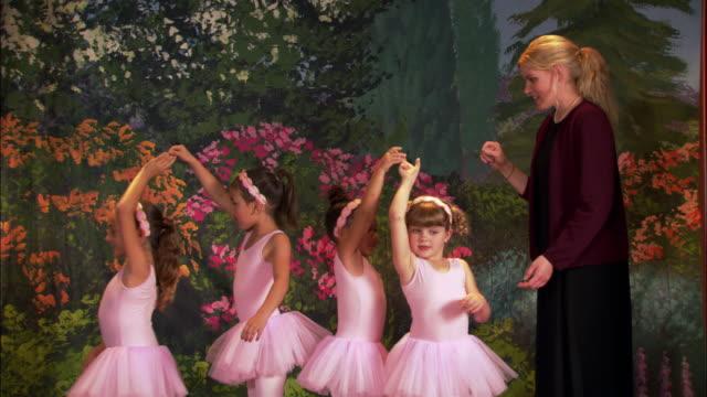 medium shot girls in tutus spinning each other around on stage / teacher helping them twirl - pacific islander teacher stock videos & royalty-free footage