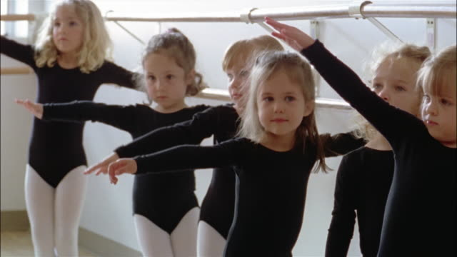 medium shot girls wearing leotards holding onto barre and stretching out arms and bending in ballet class - barre stock videos and b-roll footage