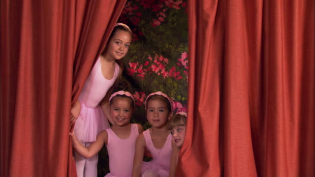 Medium shot girls wearing leotards on stage looking through curtain and posing for photos