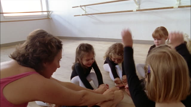 medium shot girls wearing leotards raising arms overhead and reaching for their toes n ballet class - letterbox format stock videos & royalty-free footage