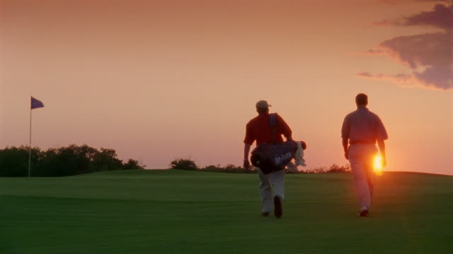 Medium shot golfer and caddy walking on golf course at dusk / Bay Harbor, Michigan