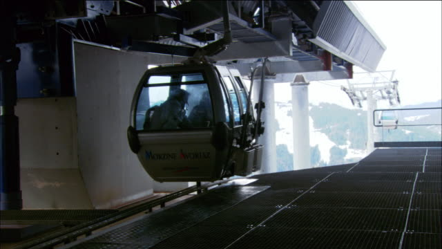 medium shot gondola stopping at platform / man and woman exiting gondola with skis and poles / morzine, france - abschied stock-videos und b-roll-filmmaterial