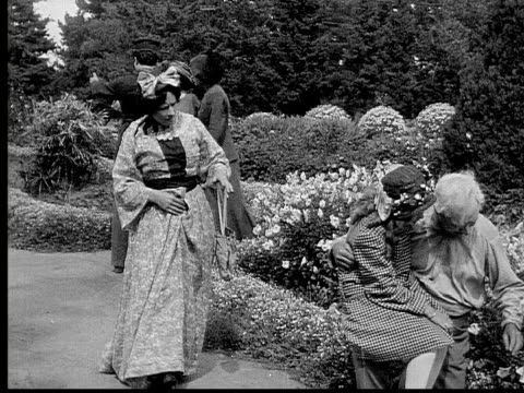 1913 b/w medium shot grandfather and granddaughter talking in garden before woman pulls at girl and grandfather protects her / usa  - 1913 stock-videos und b-roll-filmmaterial