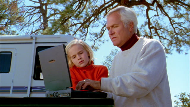 Medium shot grandfather and granddaughter using laptop computer outdoors