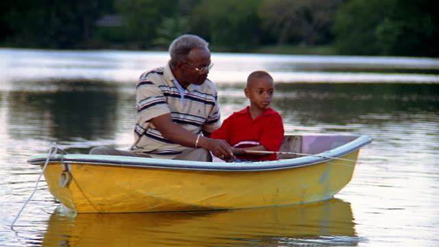 stockvideo's en b-roll-footage met medium shot grandfather and grandson fishing in canoe on lake - vissen buitensport