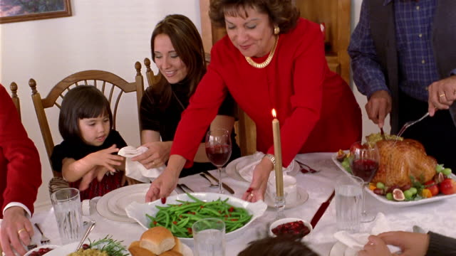medium shot grandfather carving turkey and grandmother placing food on dining table for christmas dinner - carving food stock videos & royalty-free footage