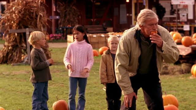 medium shot grandfather scaring children with pumpkin fangs / children running away - dentures stock videos and b-roll footage